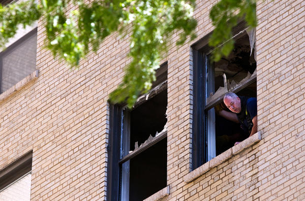 A member of the Chicago Fire Department looks out the scene of a fire in a 6th floor apartment in a high rise on east Elm in Chicago.
