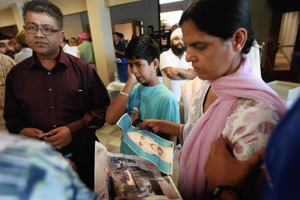 Members of the Oak Creek Sikh community look over a copy of a mug shot of Wade Michael Page during an informational gathering at the Salvation Army Community Center in Oak Creek, Wis. Page is reported to have opened fire at the Sikh Temple of Wisconsin  in the suburban Milwaukee town of Oak Creek, killing six people before being killed by police during a shootout.