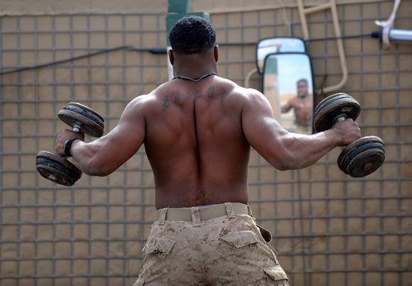 A marine lifts weights at the Amir Patrol Base's Iron yard