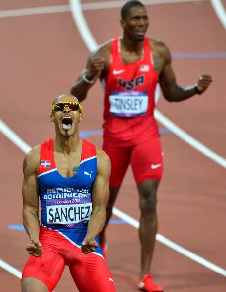 Dominican Republic's Felix Sanchez celebrates after winning the men's 400m hurdles, finishing ahead of silver medalist Michael Tinsley of the United States, rear.