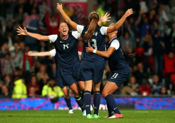 Abby Wambach, left, and Sydney Leroux, right, congratulate forward Alex Morgan after she scored the winning goal in injury time of the second overtime period against Canada to advance to the women's soccer final.
