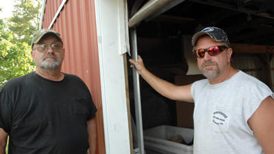 As thefts increase at the Berlin Community Grove board members have had to spend money being put aside or improvement projects. Grove President Dave Holliday and Treasurer Brad Flick stand beside a damaged garage door where thieve pried their way in.