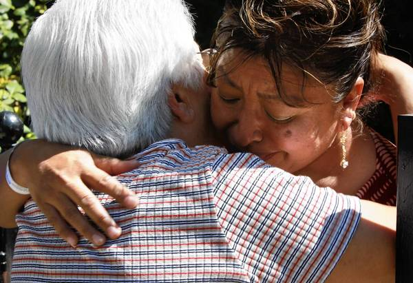 A neighbor comforts Margarita Avila, who was rescued by firefighters Sunday in the Little Village neighborhood.