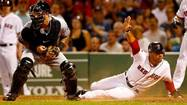 Mike Aviles #3 of the Boston Red Sox slides safely into home plate to score