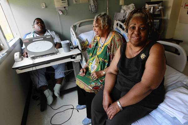 In July, Byron Moore sits with his grandmother, Alverta Moore, and his aunt, Neomie McCarthy, in the University of Chicago Medical CenterHospital in Chicago. Red tape kept him from leaving.