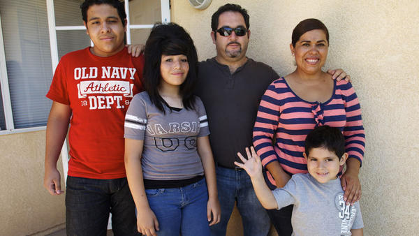 The Becerra family stands on the porch of their new home bought through a county Neighborhood Stabilization Program on Monday. The Becerras are the first to take advantage of this program. FROM LEFT: Jorge, 15, Genesis, 13, Jorge Becerra Sr., his wife Adriana and Jacob, 4.