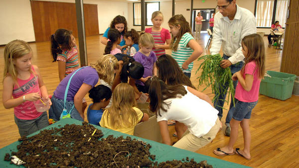 "Vincent ""Vince"" Zazueta, USDA's urban agriculture adviser, shows Girl Scouts how to grow a beautiful garden during the Girls Scout Outreach Summer Camp at the Veterans Memorial Hall in Imperial on Monday."