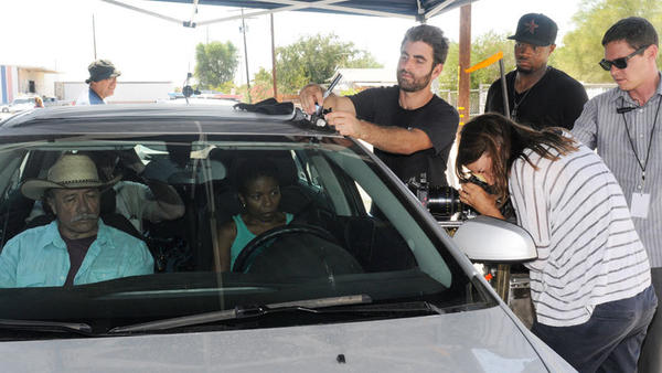 "Film crew members make adjustments to a car-mounted camera as actors Edward James Olmos and LisaGay Hamilton wait in the front seats in Calexico on Monday afternoon during the filming of the feature film ""Go For Sisters."""