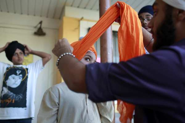 Kirpajot Singh, 6, from Westlake Village, gets help with his turban from Taranjot Singh, 16, before the start of services Monday at the Khalsa Care Foundation, a Sikh temple in Pacoima.