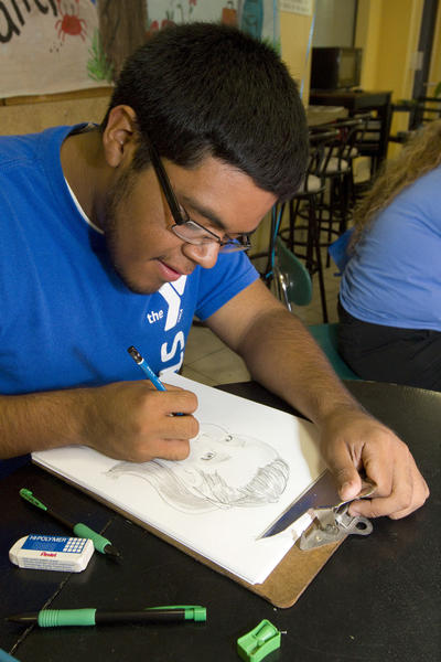 "YMCA camp counselor Jonathan Hurtado sketches a portrait of Samantha Fortin, 3, during the YMCA's Boynton Beach location during the YMCA of Palm Beach County's ""Back-to-School Bash,"" which took place on Aug. 4."