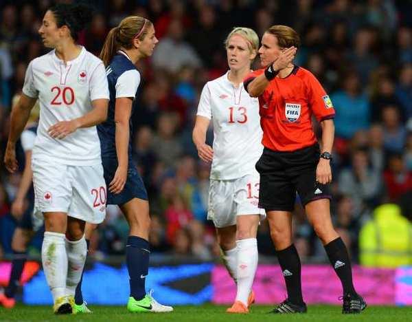 Referee Christina Pedersen, right, speaks to players during Monday's U.S.-Canada women's soccer match.