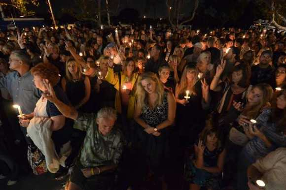 Friends and community members gather for a candlelight vigil outside the the Salon Meritage in Seal Beach to mourn the eight people who were shot and killed when a man open fired in the salon in October 2011.
