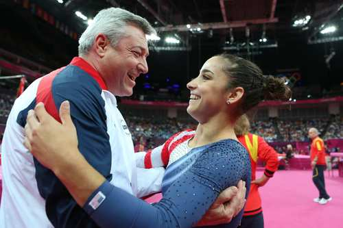 Aly Raisman of the United States hugs coach Mihai Brestyan after winning the gold medal in the floor exercise.