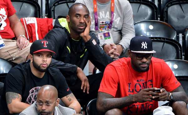 Men's basketball team members, from left, Deron Williams, Kobe Bryant and LeBron James watch the women's  U.S.-Canada game.