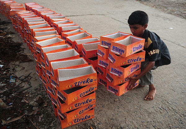 A Bangladeshi child lifts shoe boxes at a factory in Dhaka on August 7, 2012. Bangladesh is one of the poorest nations with 40 percent of its 144 million people living on less than one dollar a day.