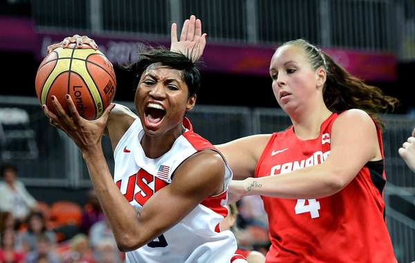 Angel McCoughtry, left, of the United States, grabs an offensive rebound from Canada's Krita Phillips in a women's basketball quarterfinal match. The Americans won, 91-48.