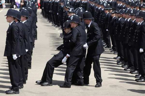 A British policeman faints during a parade. Tendency to faint is partly rooted in genetics, a study suggests.