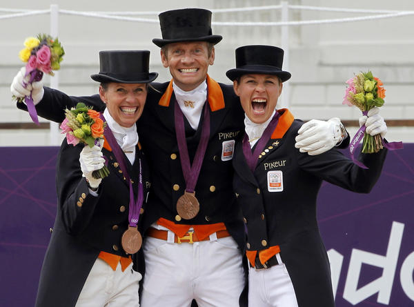 Photos: The 2012 London Olympics: Bronze medallists Netherlands Anky van Grunsven, Edward Gal and Adelinde Cornelissen (L-R) celebrate during the equestrian dressage team victory ceremony.