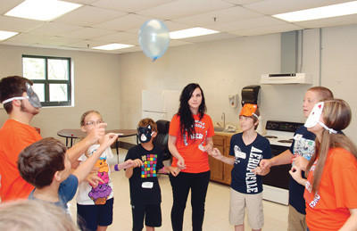 WEB leader Jacob Sullivan, left, Camille Felts and Michelle Webber, in orange shirts, join sixth-grade students in keeping a balloon in the air while linking pinky fingers.