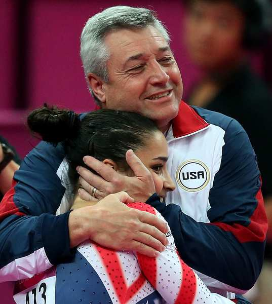 Coach Mihai Brestyan hugs American gymnast Aly Raisman  after she completed her routine in the women's floor exercise. She won the gold medal, becoming the first American woman to win gold in that event.