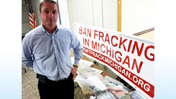 Cal Tillman, former mayor of Dish, Texas, poses near a table of photos of gas well-drilling operations in Northern Texas. He warned that additional pipelines, processing facilities and wells will be coming to Michigan.