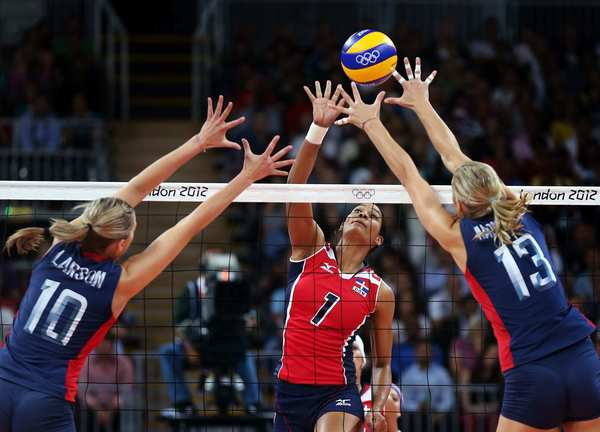 Annerys Victoria Vargas Valdez of the Dominican Republic  spikes the ball as Jordan Larson, left, and Christa Harmotto of the United States defend.