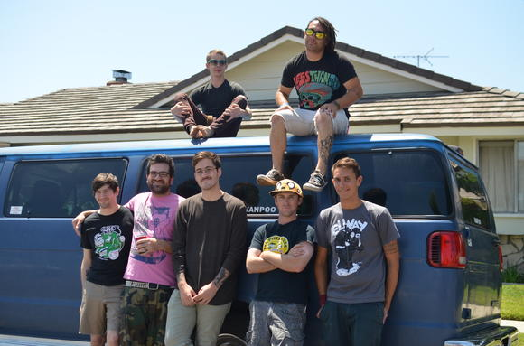 "Save the Swim Team stands in front of ""Vanpoo,"" the band's tour van, outside its rehearsal space in Fountain Valley."