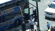 Police and bystanders tend to a woman hit by a Megabus near Union Station this afternoon. Casey Hill, for the Tribune
