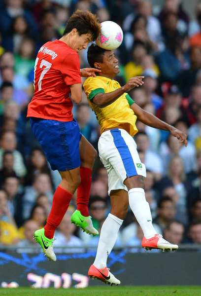 South Korea's Kim Hyun-sung, left, vies for a header with Brazilian defender Alex Sandro.