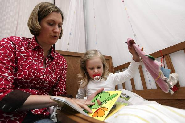 A mother reads a bedtime story to her 3-year-old daughter on June 6, 2012, in Berlin.