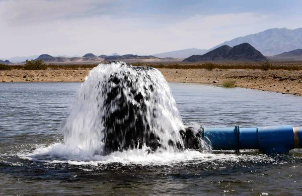Water pours out into a spreading basin which holds water from pilot well number 1 used for testing and is part of a possible water storage component on Cadiz Ranch. Cadiz Inc. hopes to build a conveyance pipeline along railroad tracks to export groundwater from the Mojave Desert.