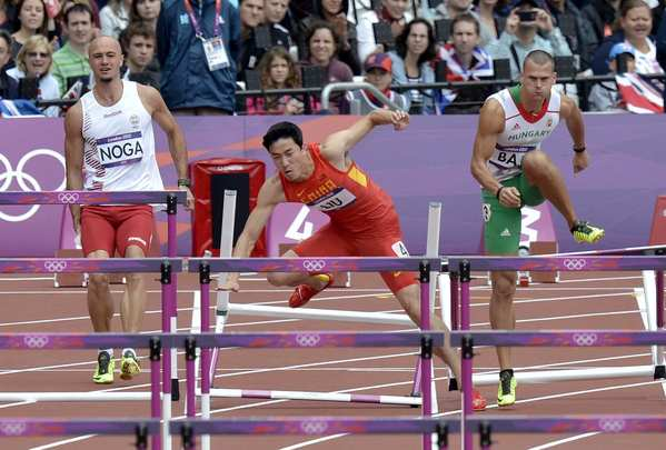 China's Liu Xiang, center, falls between Hungary's Balazs Baji, left, and Poland's Artur Noga duing a men's 110-meter hurdles heat.