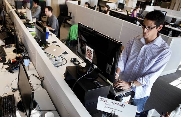 Sales analyst Joel Hadley, right, has abandoned the chair for a standing desk during his workday at the Groupon offices in Chicago.