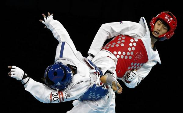 South Korea's Daehoon Lee, right, fights against Thailand's Pen-Ek Karaket during their Men's 58kg preliminary round match at the ExCel venue during the London Olympic Games.