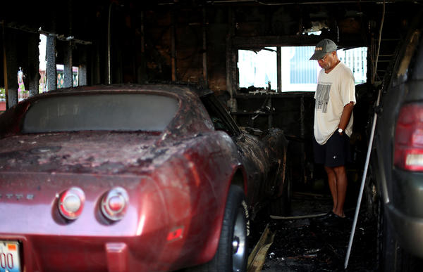 Ty Hanson looks at his damaged 1975 Corvette Stingray in his garage in the 1600 block of Berwyn in Chicago. Six Andersonville garages were affected by a fire overnight.