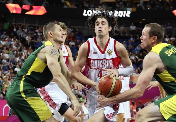 Alexey Shved, center, of Russia attempts to move the ball between Renaldas Seibutis, left, and Darius Songaila, right, of Lithuania in the first half during the Men's Basketball quaterfinal game on Day 12 of the London 2012 Olympic Games.