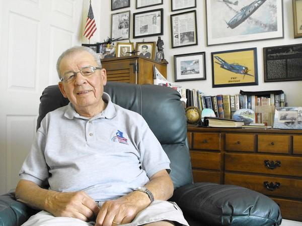 Alfred Zelent sits in the den of his Gurnee home, which is decorated with World War II memorabilia