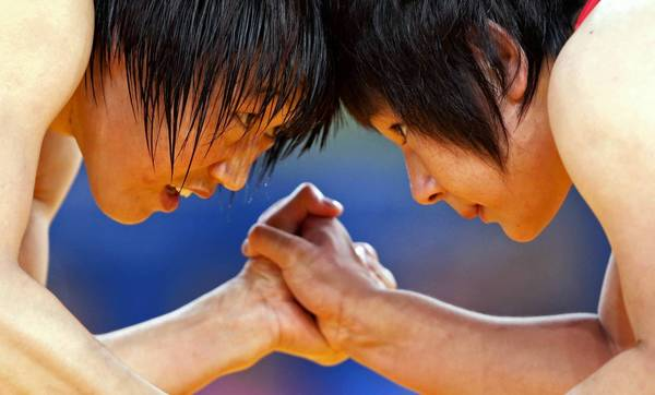 China's Ruixue Jing, left, fights with North Korea's Un Gyong Choe in their Women's 63Kg Greco-Roman wrestling match during the London 2012 Olympic Games.