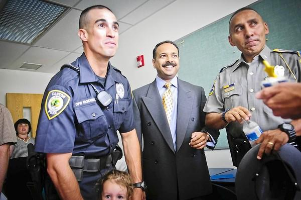 Canton Police Department officer David Rodriguez (L) and his 2-year-old daughter Avery Rodriguez talk with Lawrence Terra (middle), Canton's new police captain, and Lieutenant David Rosado of Troop H.