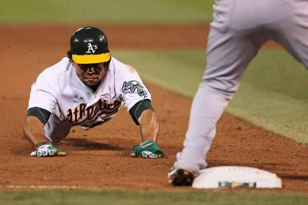 Oakland Athletics center fielder Coco Crisp (4) dives to steals third base against Los Angeles Angels third baseman Alberto Callaspo (6) during the fifth inning at O.co Coliseum.