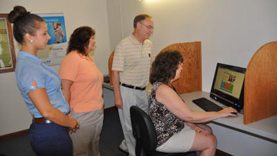 Your Health Insurance Shop individual product specialists Alicia Formica and Cristy Pritts along with VCS Group President Glenn Miller watch as manager of individual products Maureen Snyder shows how  people can use the computers to compare plans. The insurance retail shop is located 130 West Main Street.