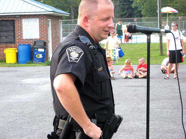 Hancock Police Chief T.J. Buskirk welcomes the crowd to Tuesday evening's National Night Out Against Crime event in Widmeyer Park.