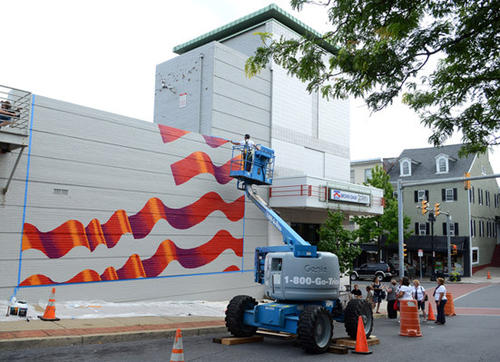 Scott LoBaido of Staten Island paints a large American flag on west wall of Easton's State Theater to honor America's service members