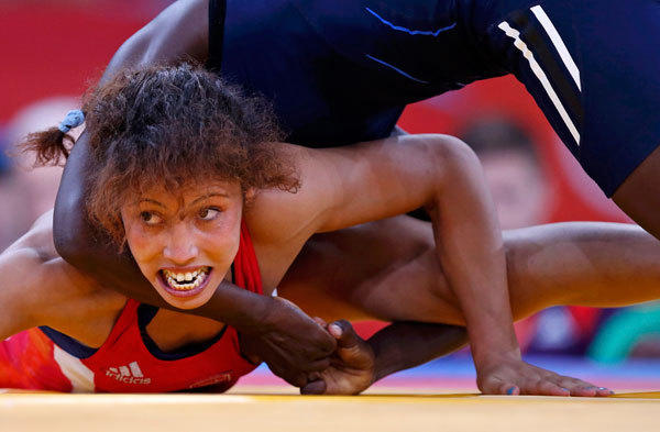 Senegal's Isabelle Sambou (in blue) fights with Tunisia's Maroi Mezien on the repechage of the Women's 48Kg Greco-Roman wrestling at the ExCel venue during the London 2012 Olympic Games August 8, 2012.