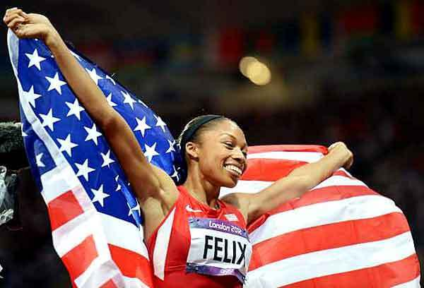 Allyson Felix holds the U.S. flag as she takes a victory lap following her gold-medal run in the 200 meters Wednesday night in London.