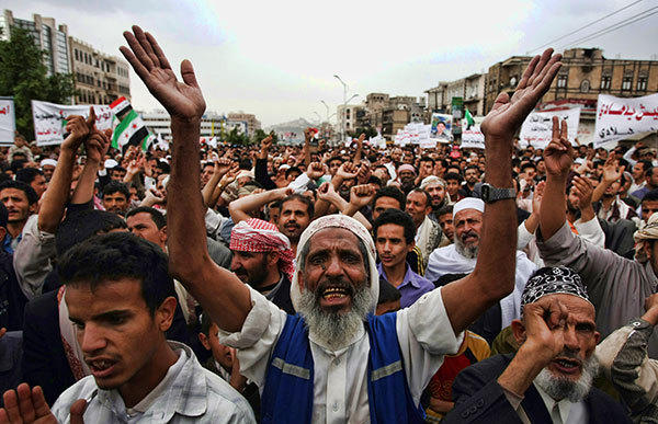 Yemeni men chant slogans as they rally outside the residence of Yemeni President Abdrabuh Mansur Hadi, in Sanaa on August 8, 2012, in support of his decision to strip Ahmed Saleh, the son of former Yemeni president Ali Abdullah Saleh, of part of his military command.