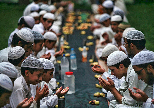 Muslims offer prayers before having their Iftar (fast-breaking) meal during the holy month of Ramadan at a madrasa or religious school on the outskirts of Jammu August 8, 2012.