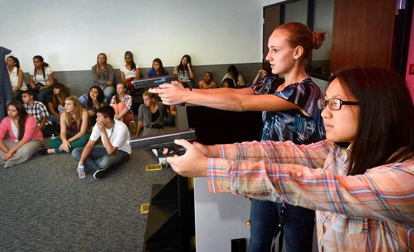 "Jennifer Aufill, left, and Jessica Jin take their best ""shot"" at an electronic training device at the Orange County Sheriff's Department in Orange during the the 13th annual Summer Youth Education Conference."
