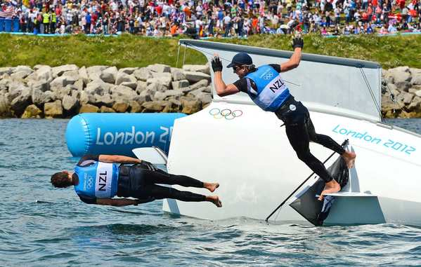 New Zealand's Blair Tuke, left, and Peter Burling leap into the water after winning silver in the 49er sailing class.