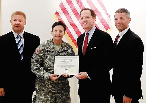 U.S. Sen. Pat Toomey, second from right, presents a commendation to outgoing Letterkenny Commander Col. Cheri Provancha, second from left, during a visit to Letterkenny Wednesday. Also pictured are state Sen. Richard Alloway, left, and state Rep. Rob Kauffman.